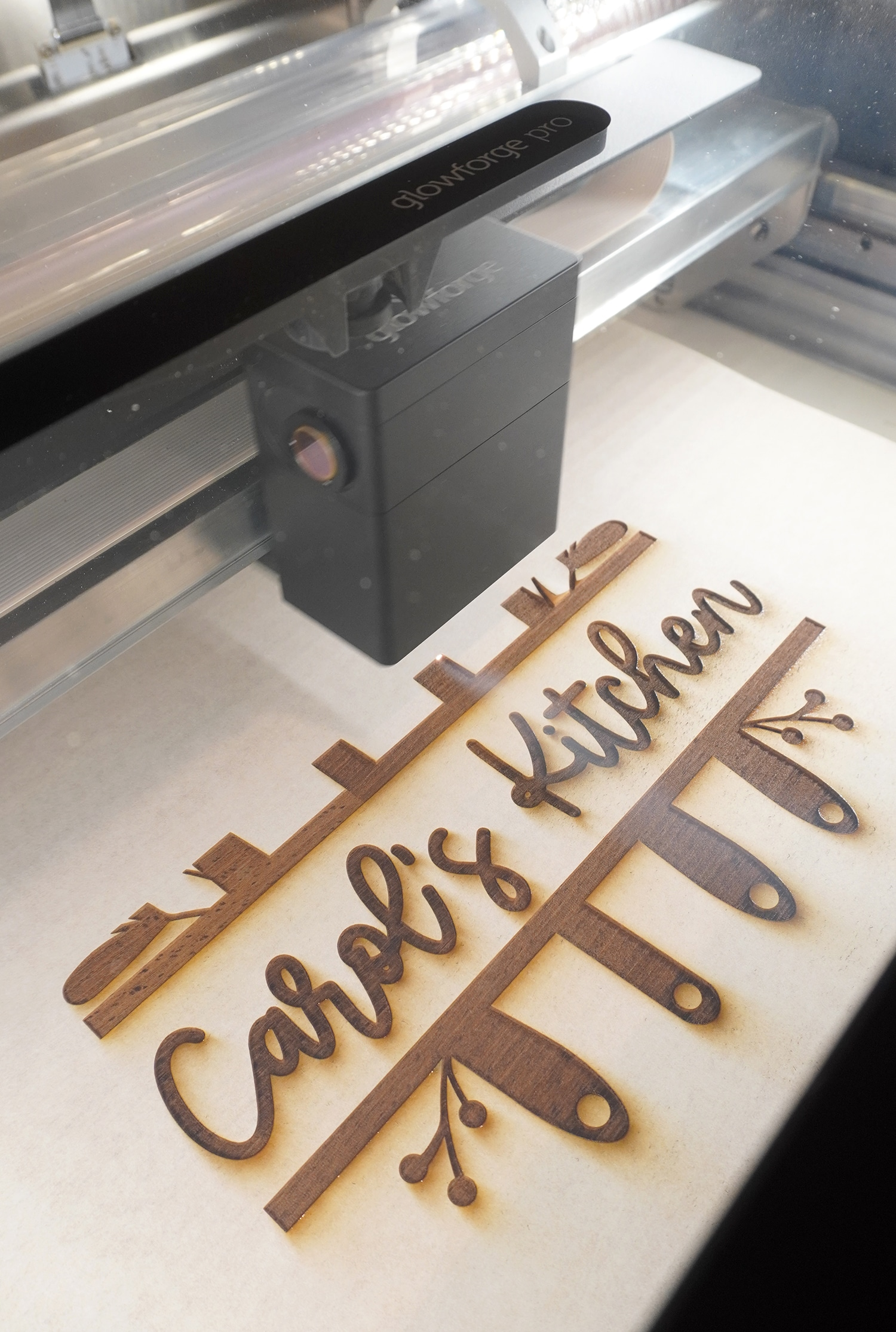 "Glowforge Pro Engraving a Cutting Board with ""Carol's Kitchen"" design"