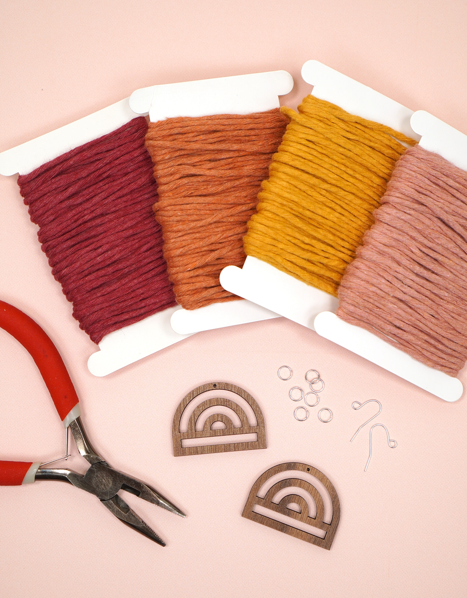 Supplies to Make Macrame Rainbow Earrings on peach background - cord, wooden rainbows, earring findings, and jewelry pliers