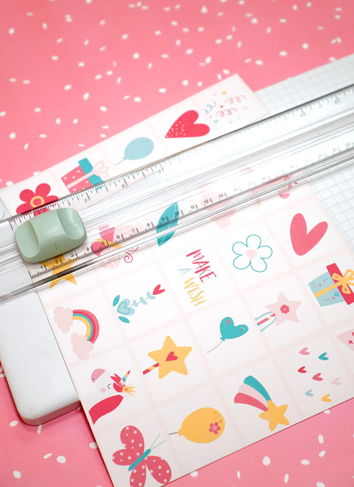 Paper trimmer cutting a sheet of Unicorn Bingo Game calling cards on a pink background