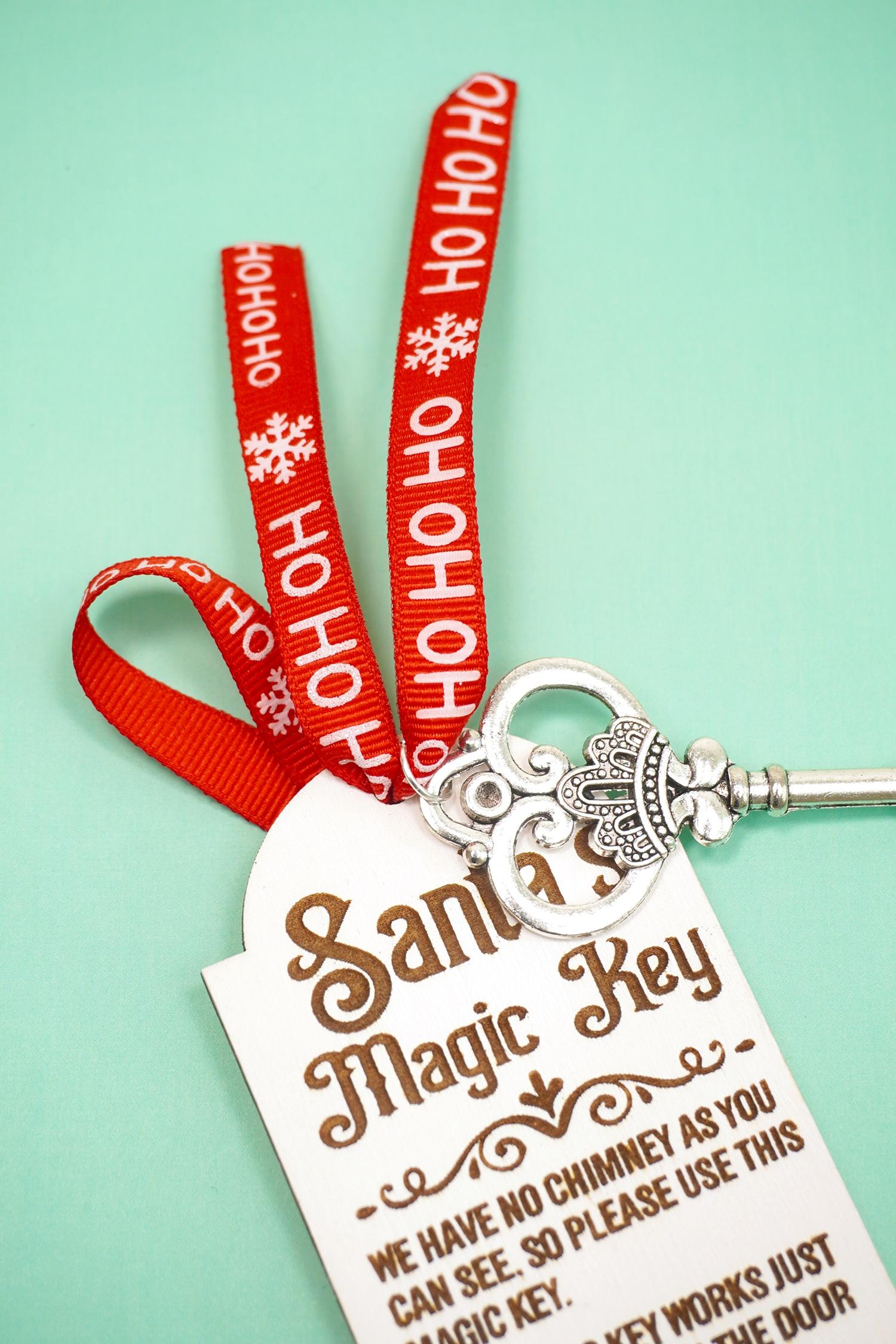 Adding a red ribbon and silver key to a laser engraved Santa's Magic Key tag