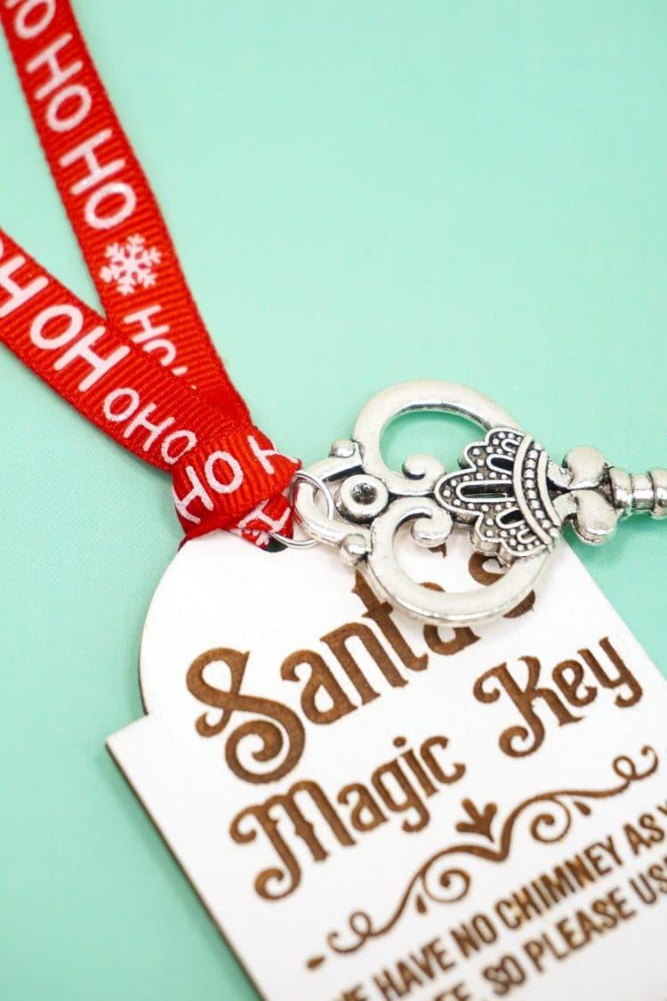 Close up of red ribbon and silver key tied to a laser engraved Santa's Magic Key tag