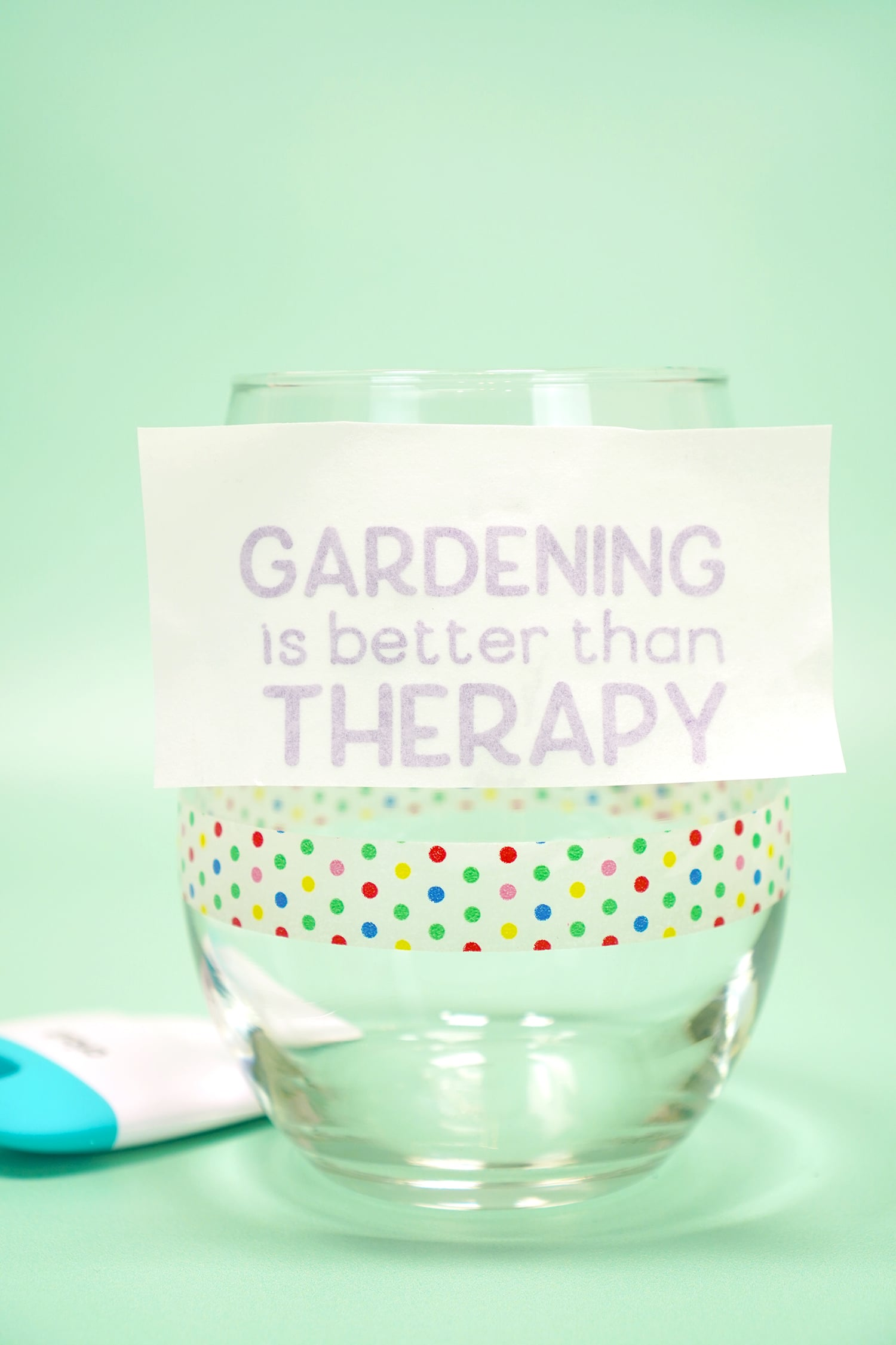 """Applying """"Gardening is Better Than Therapy"""" purple shimmer vinyl to a clear stemless wine glass on mint green background"""