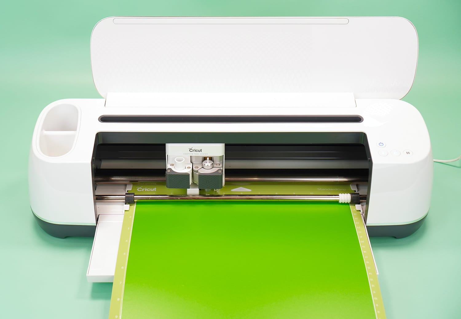Cricut Maker machine with lime green vinyl on mat on mint green background