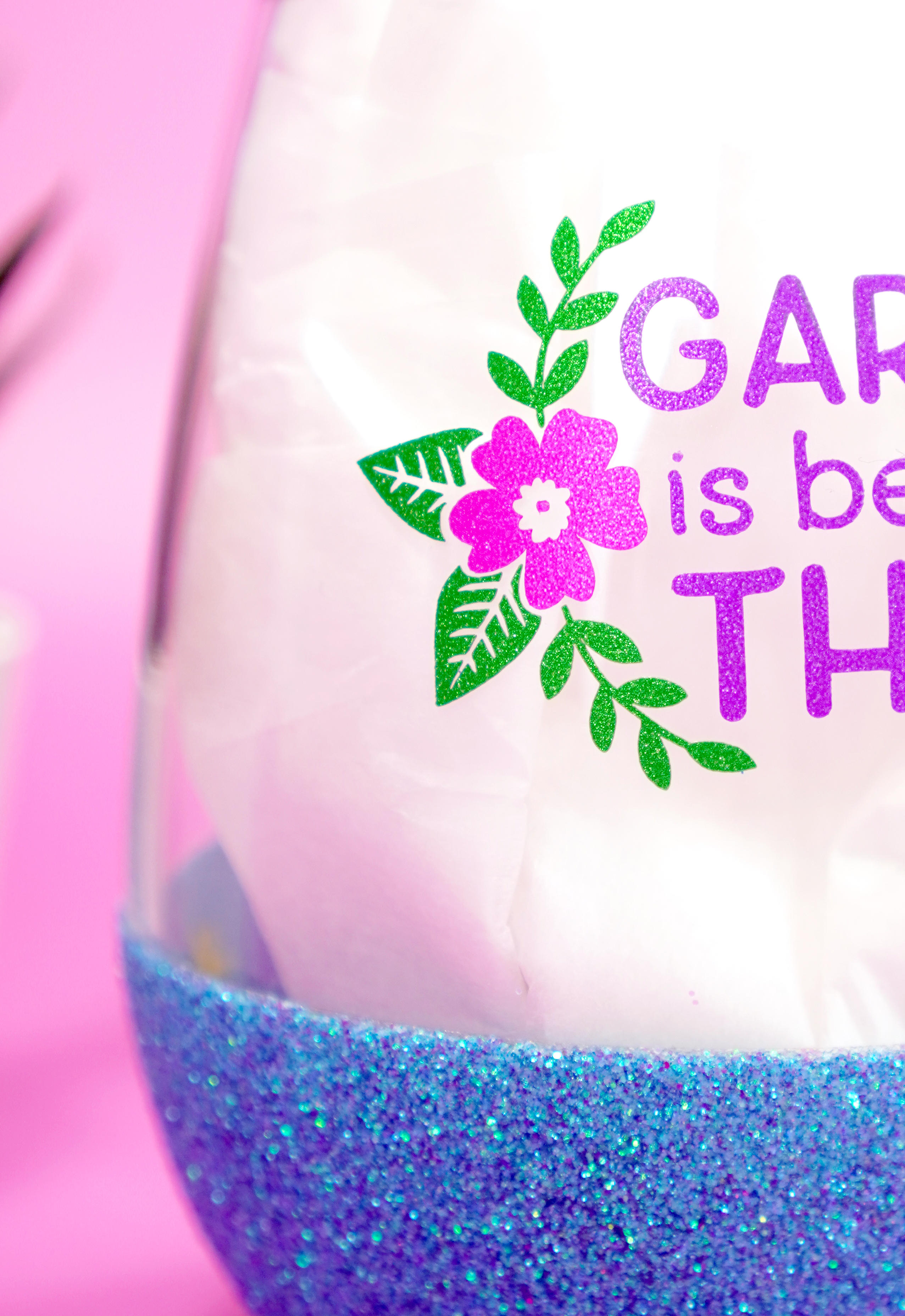 Close up of Cricut Shimmer Vinyl design on wine glass - pink flower with green leaves and vines