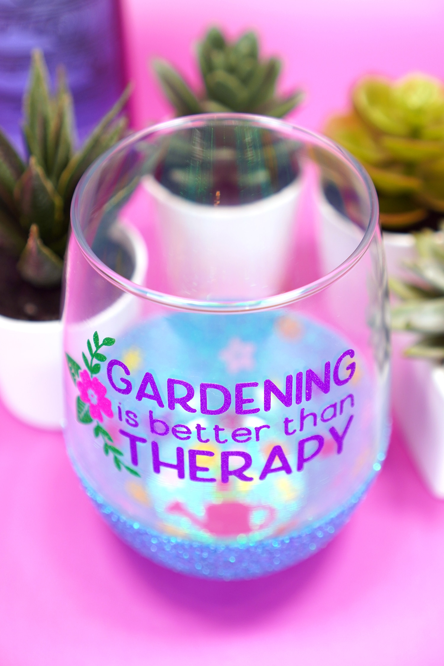 """Overhead angle shot of """"Gardening is Better Than Therapy"""" wine glass with blue glittered base and a peekaboo watering can and flowers design inside"""