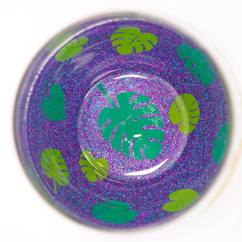 Leaf decals on the inside of a peekaboo glitter wine glass with purple multi-hued glitter