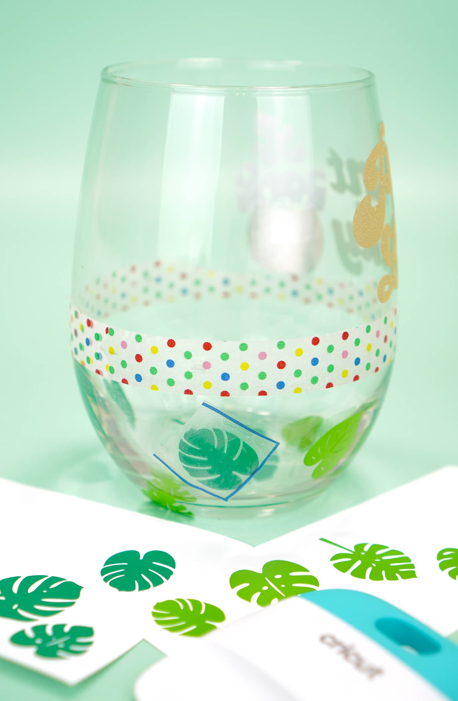Clear stemless wine glass with band of washi tape and green vinyl leaf decals applied to bottom half of glass