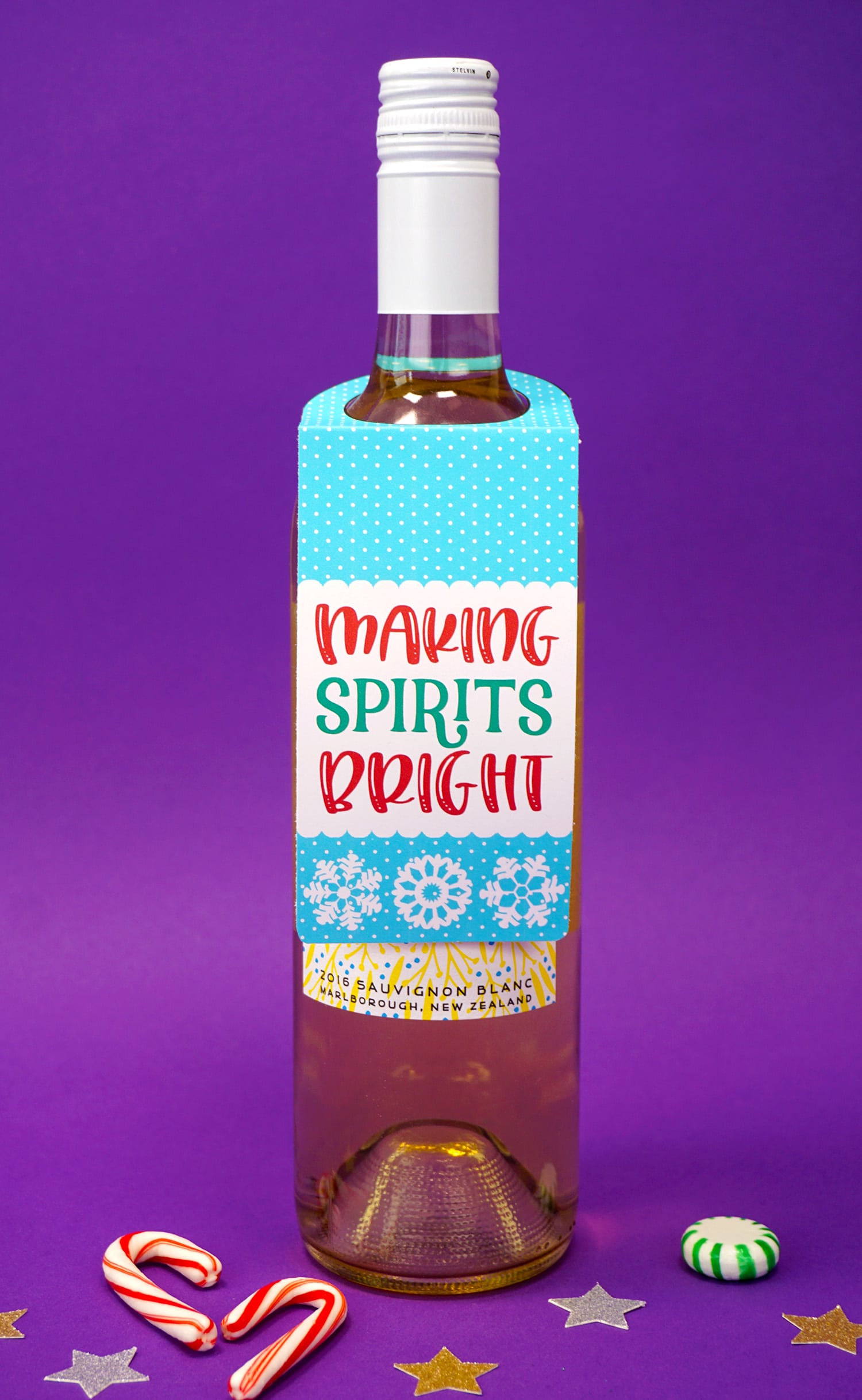 """""""Making Spirits Bright"""" Christmas wine tag on bottle on purple background with candy canes and stars"""