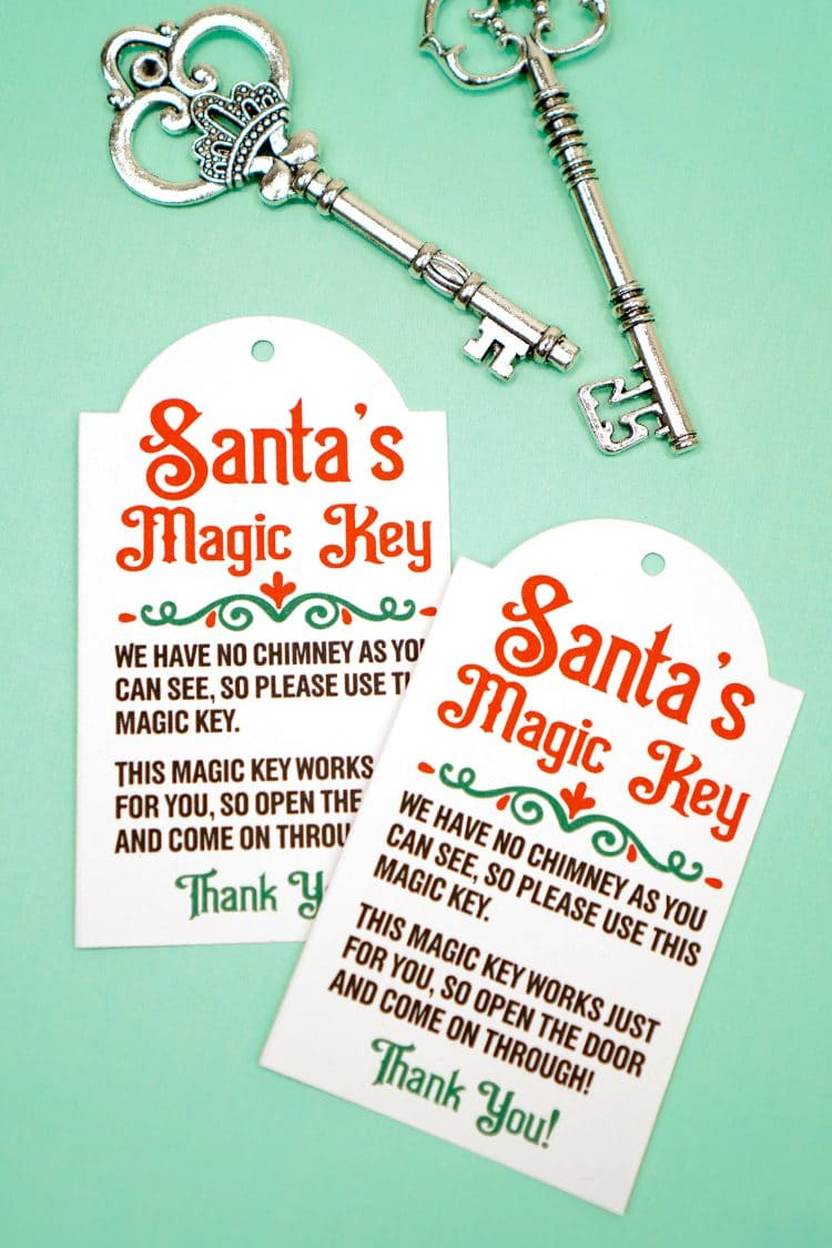 Two Santa's Magic Key printable tags and silver keys on a mint green background
