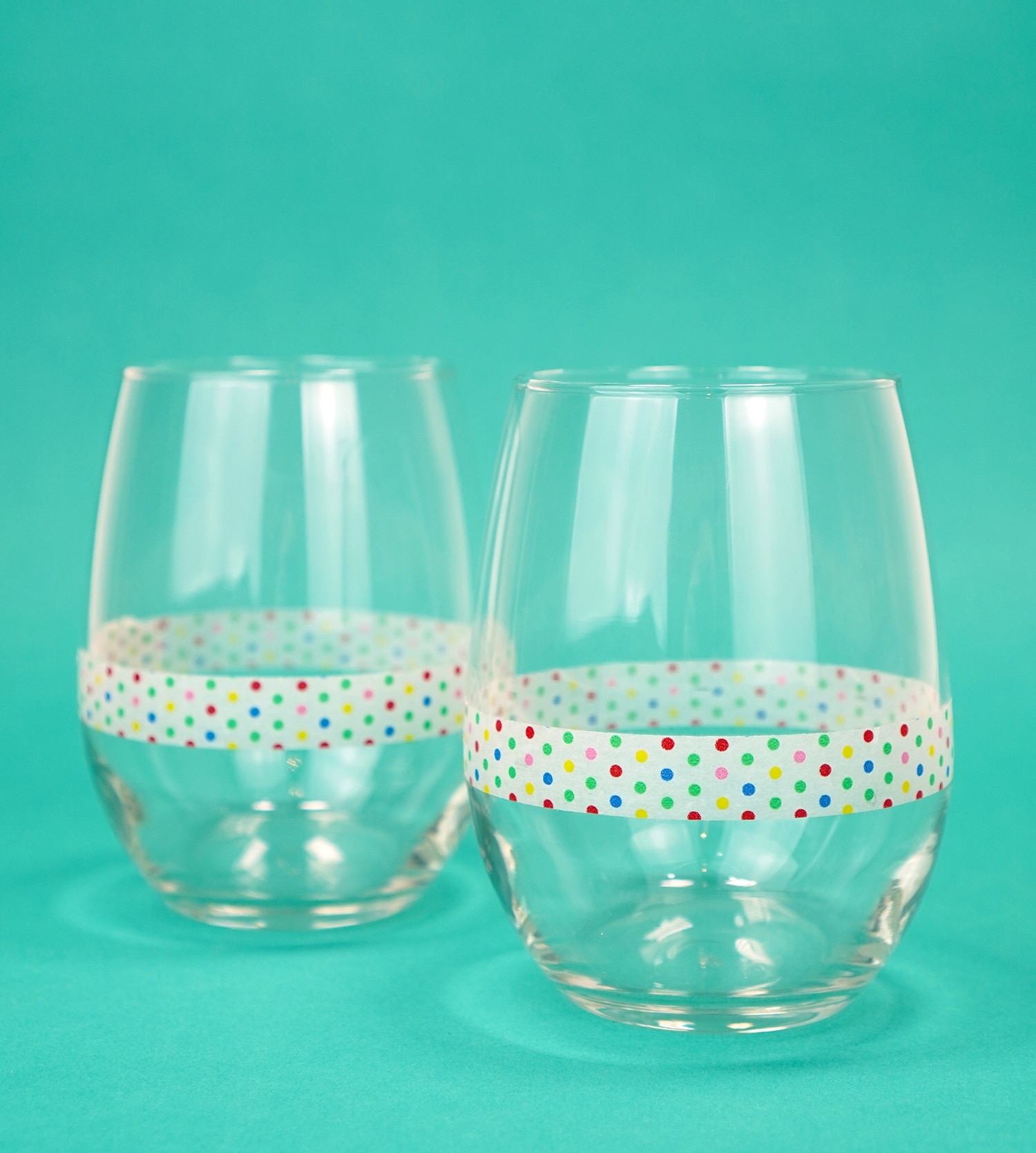 Two stemless wine glasses on teal background with a band of polka dot washi tape around each glass