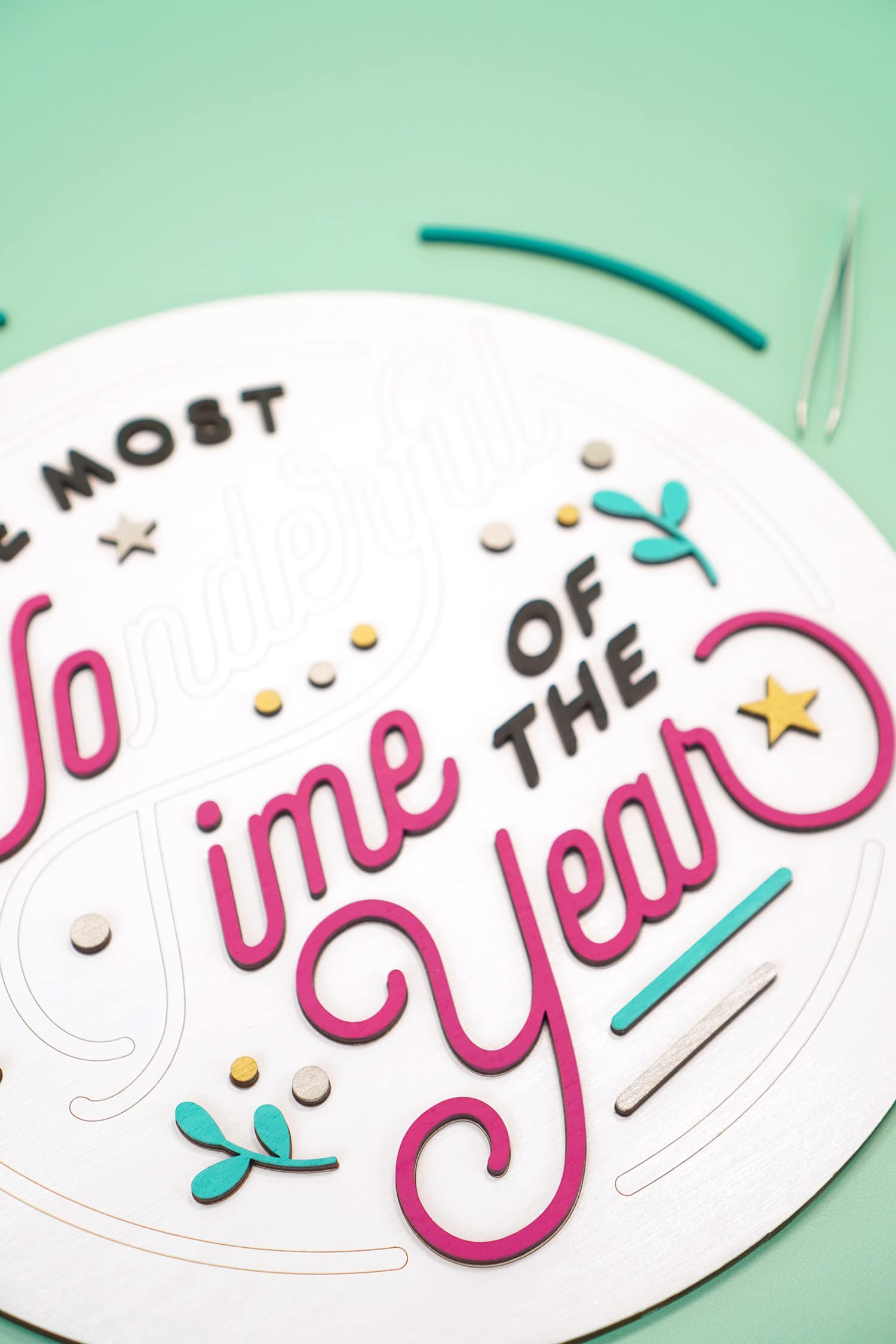Arranging Glowforge laser cut wood pieces on round wooden sign with tweezers and mint green background