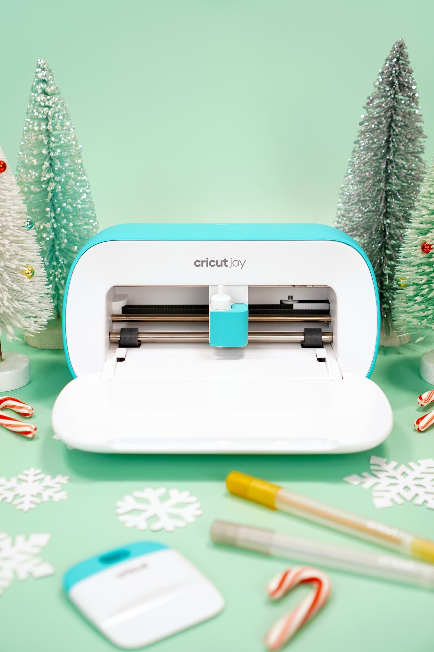 Cricut Joy machine surrounded by Cricut tools, paper snowflakes, and candy canes on mint green background