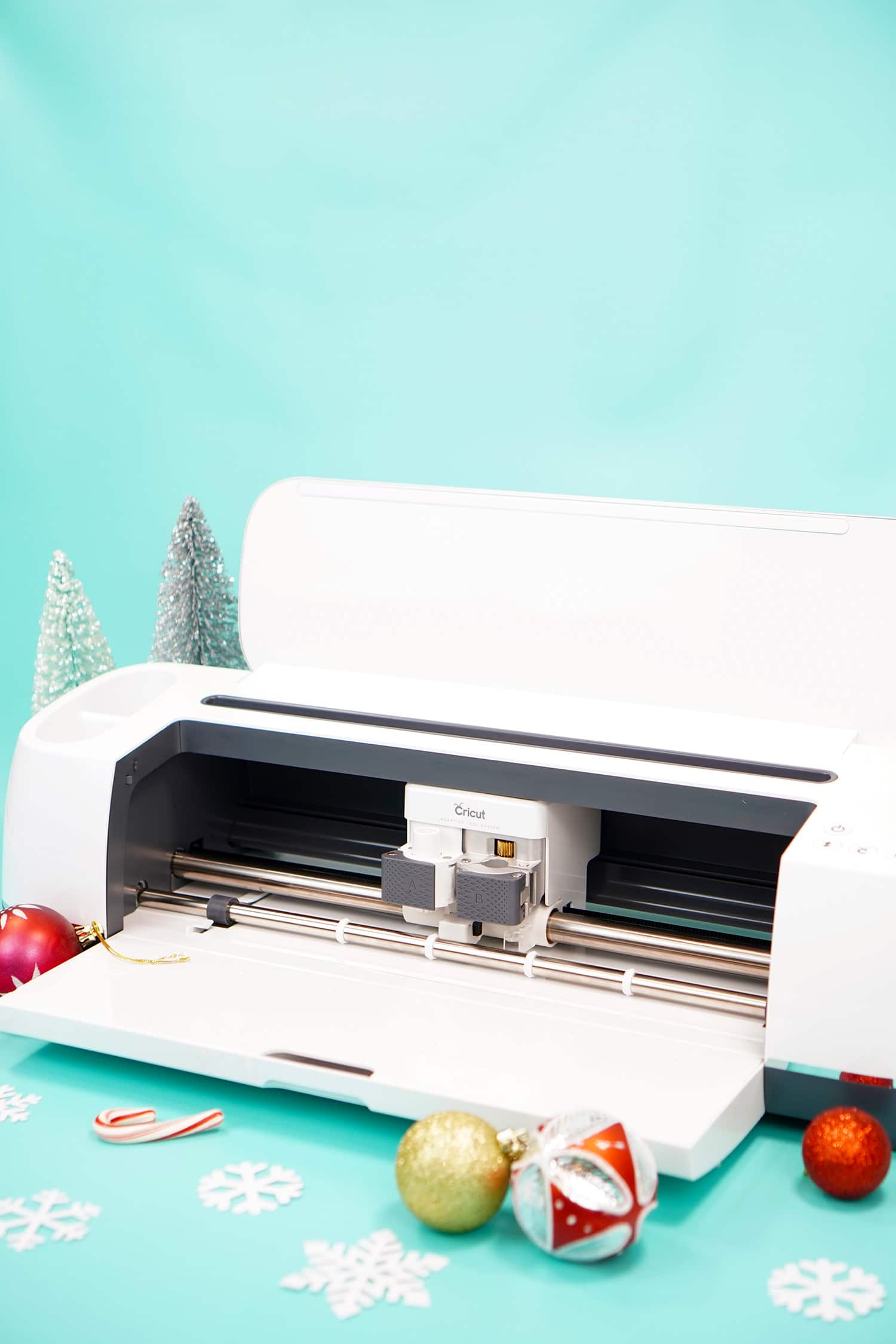 Cricut Maker machine on aqua background with white snowflakes and red and gold ornaments
