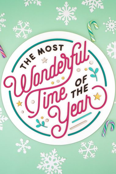 """The Most Wonderful Time of the Year"" Laser Cut Wood Sign on mint green background with white paper snowflakes and colorful mini candy canes"