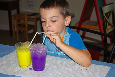 child blowing bubbles into cup of purple paint