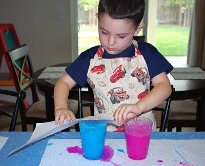 child with cup of paint