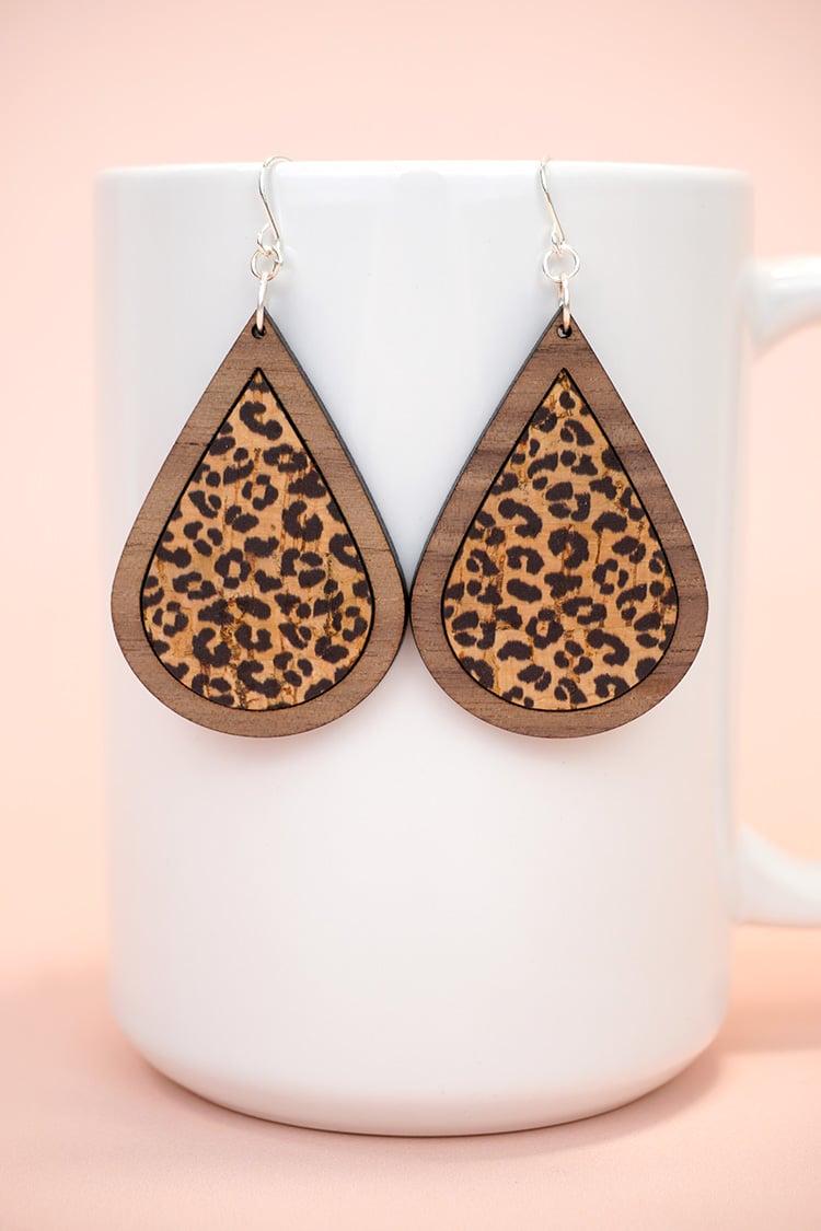 Leopard print laser cut wood earrings displayed on white mug