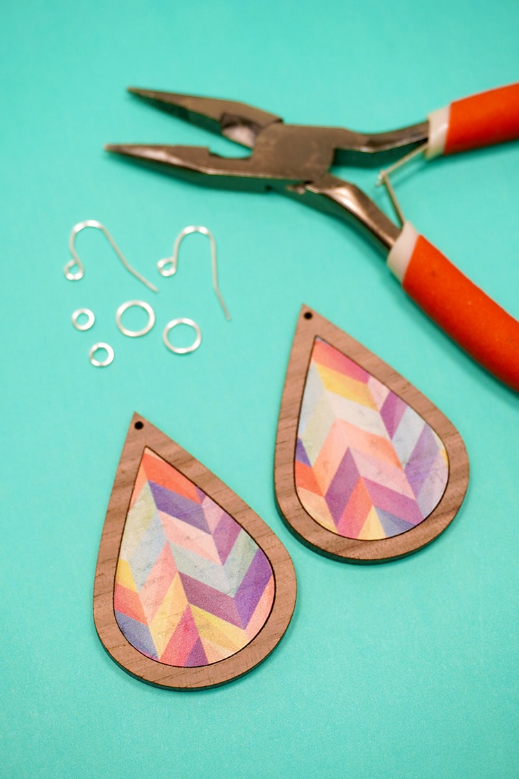 Two cork and wood teardrops on a teal background with silver jewelry hardware and pliers