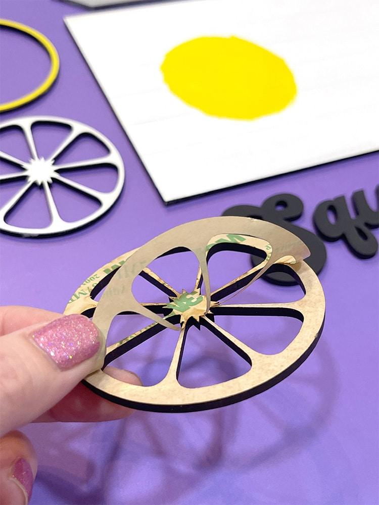 Peeling 3M adhesive tape off the back of a lemon shaped wood piece