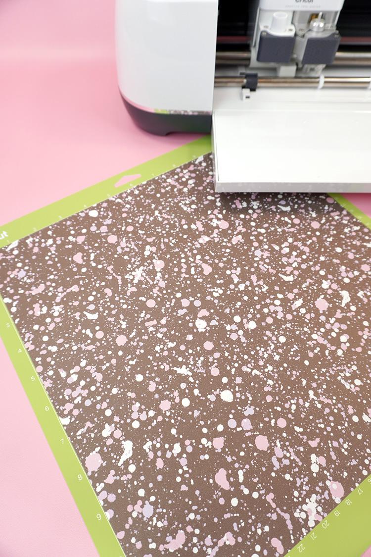 "Sheet of ""paint splattered"" Infusible Ink on a Cricut cutting mat"