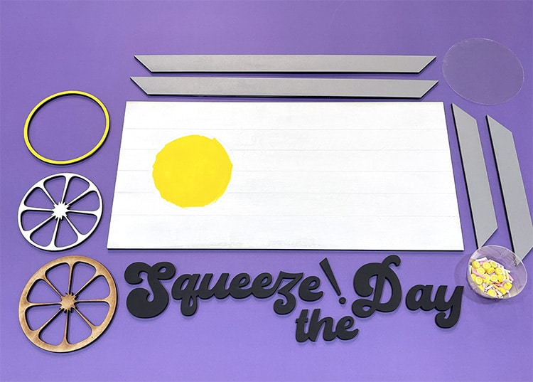 Painted laser cut wood sign pieces on a purple background