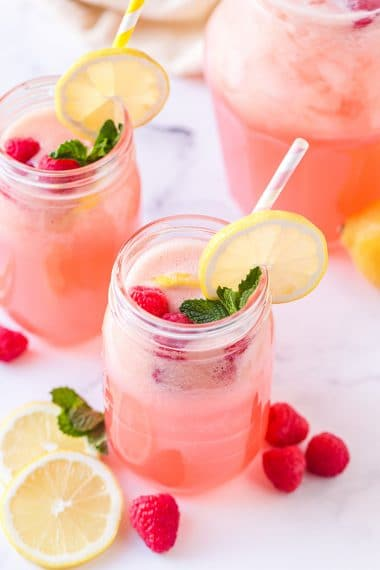 Homemade raspberry lemonade in mason jar glasses with striped straws, lemon slices, raspberries, and mint garnish