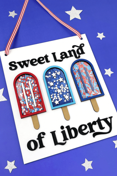 """""""Sweet Land of Liberty"""" sign with popsicles on a blue background with silver stars"""