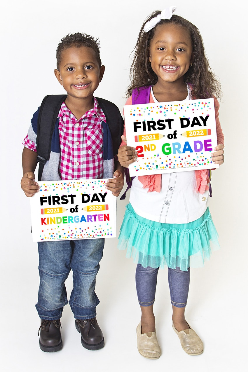 Two cute Black children holding up printable First Day of School Signs with rainbow colors