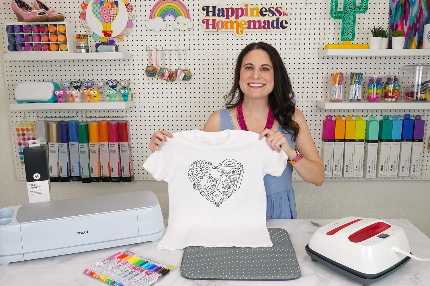 Heidi Holding Up Back to School Shirt in front of craft room pegboard of colorful supplies