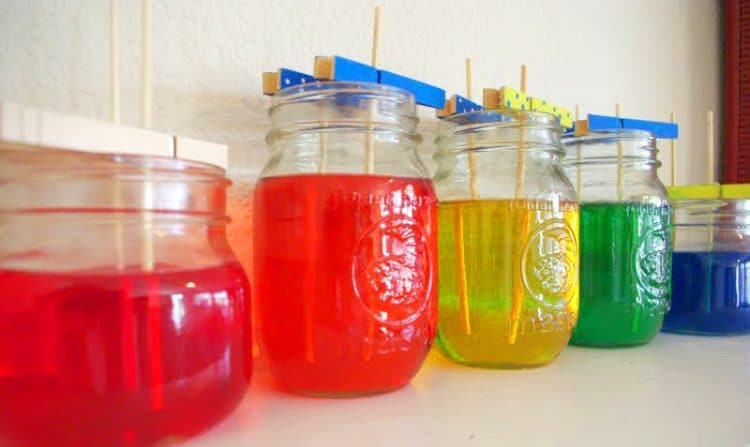 rainbow mason jars filled with sugar solution and sticks for homemade rock candy