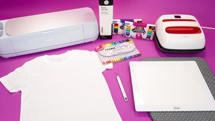 Supplies for making a back to school shirt - shirt, Cricut Maker 3, EasyPress 2, tools, and fabric markers