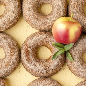 apple cider donuts with apples on yellow background