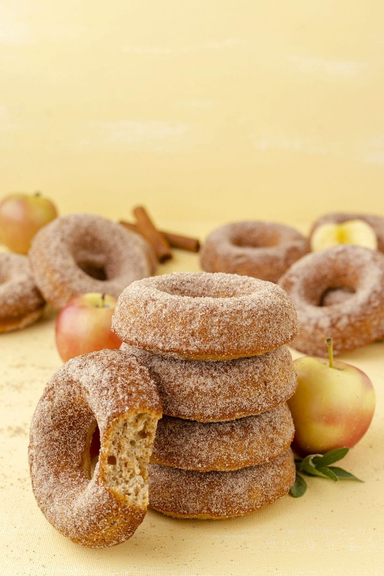 stack of apple cider donuts on yellow background with apples and cinnamon sticks