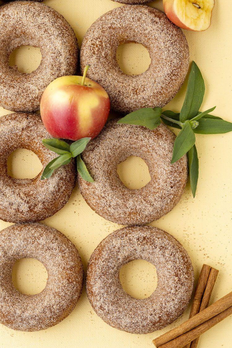 six apple cider donuts on a yellow background with apples, leaves, and cinnamon sticks