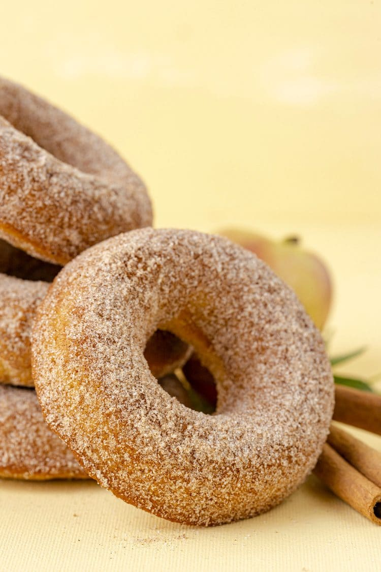 Close up of cinnamon sugar apple cider donut on yellow background