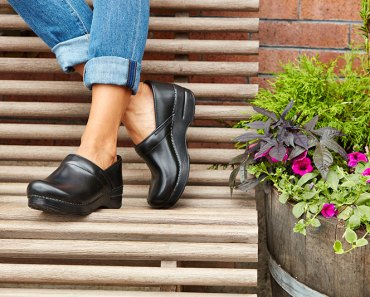 womans-black-clog-blue-jeans-on-bench
