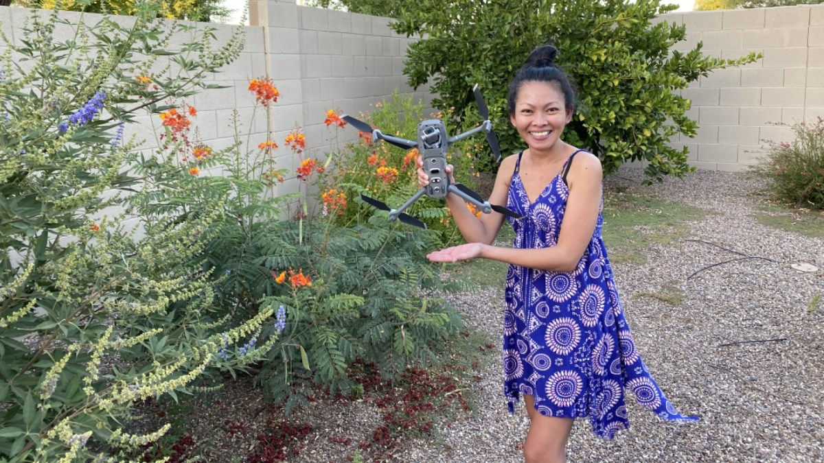 pretty filipino woman holding dji mavic 2 pro drone next to bush and flowers