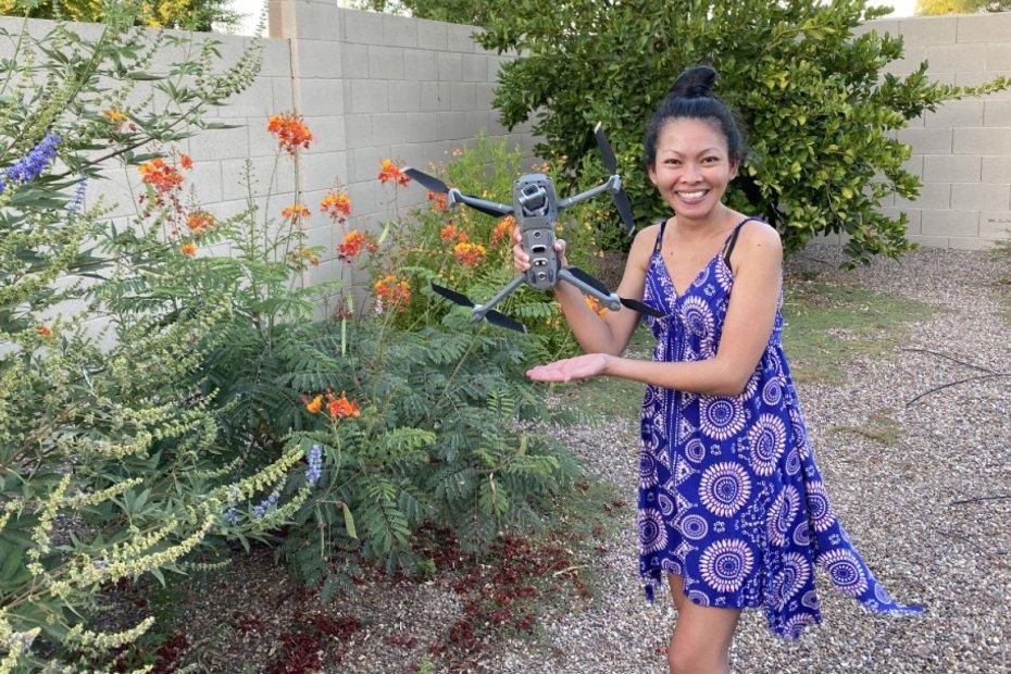 pretty filipino woman holding dji mavic 2 pro drone next to bush and flowers