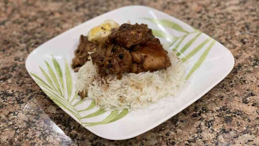 A plate with chicken, jasmin rice, eggs, and, pork filipino adobo
