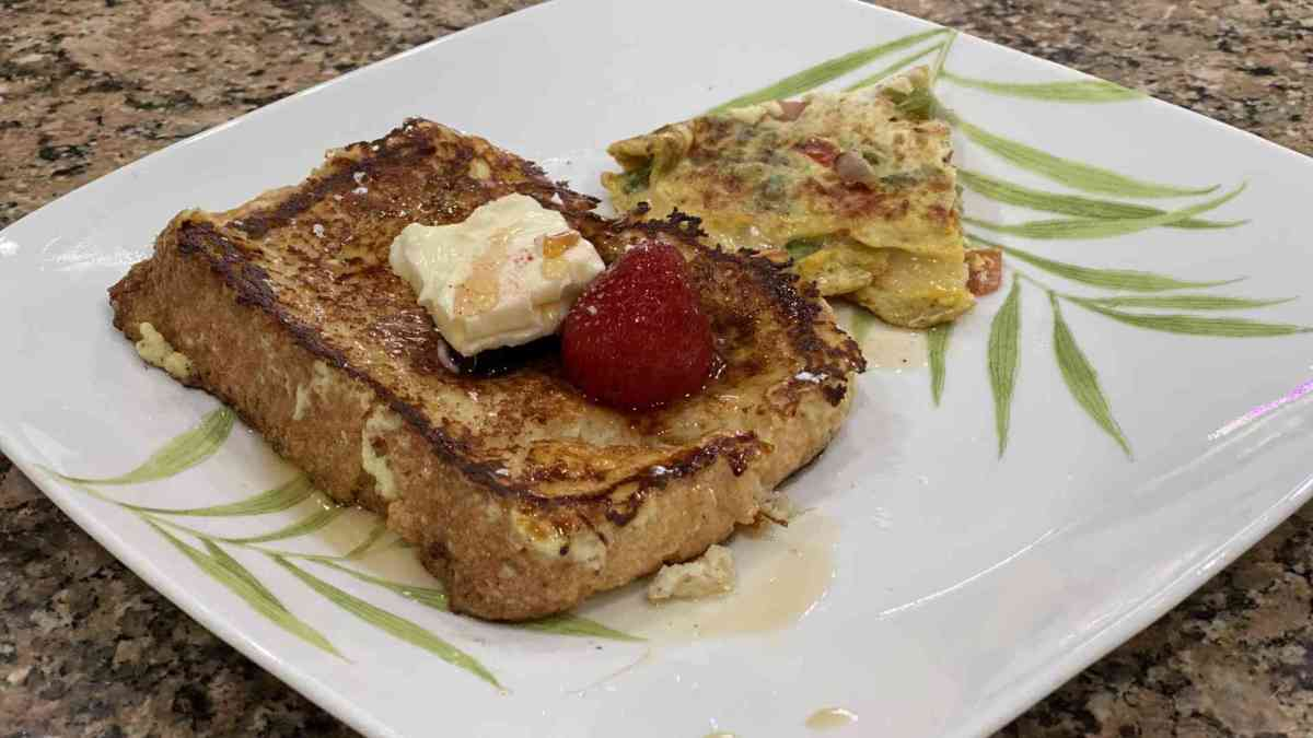 homemade french toast with butter, fruit, maple syrup and omelet on the side
