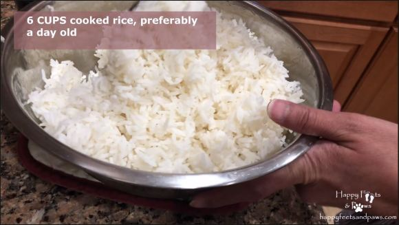 Seperating rice grain with a fork in prep for thai chicken fried rice recipe