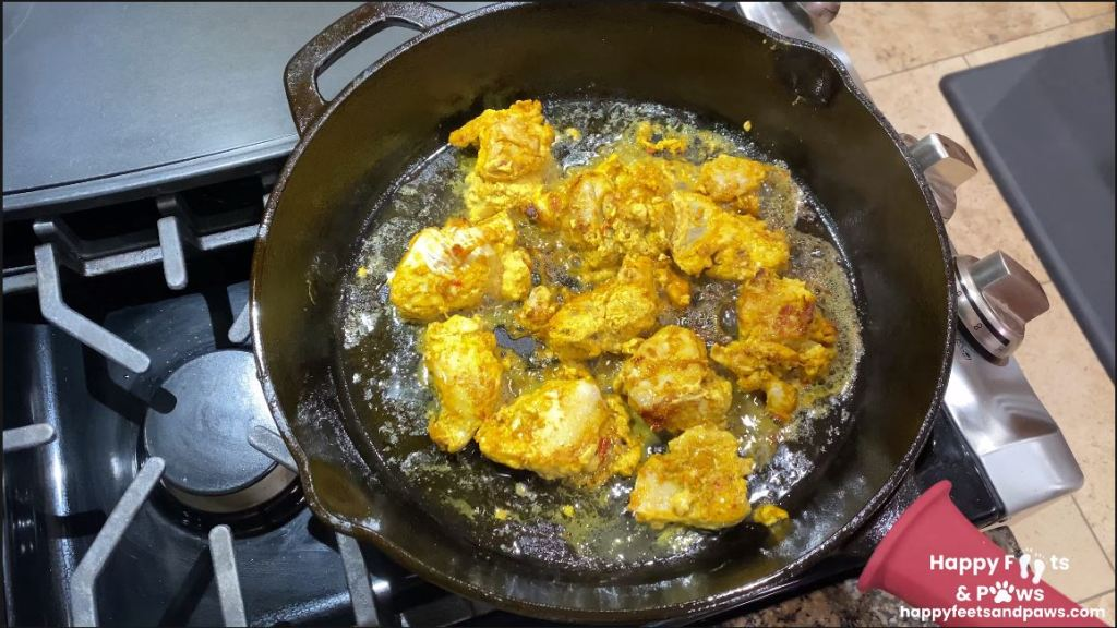 chicken being fried in a cast iron pot for chicken tikka masala recipe