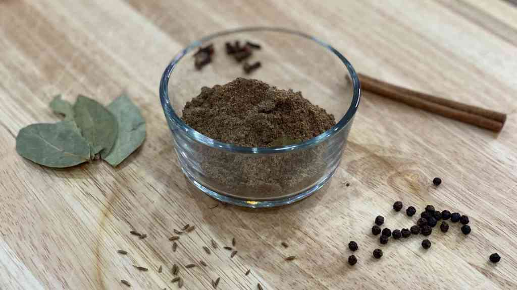 Garam Masala in a cup with ingredients used to make it on wood cutting board