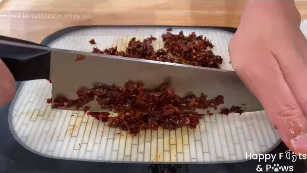 Chopping sundried tomatoes on a cutting board