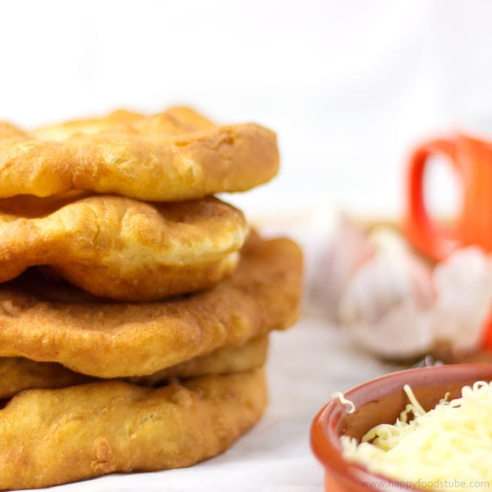 Langos is a Hungarian deep fried flat bread (made of yeast, flour & water) that is eaten while still warm.   happyfoodstube.com