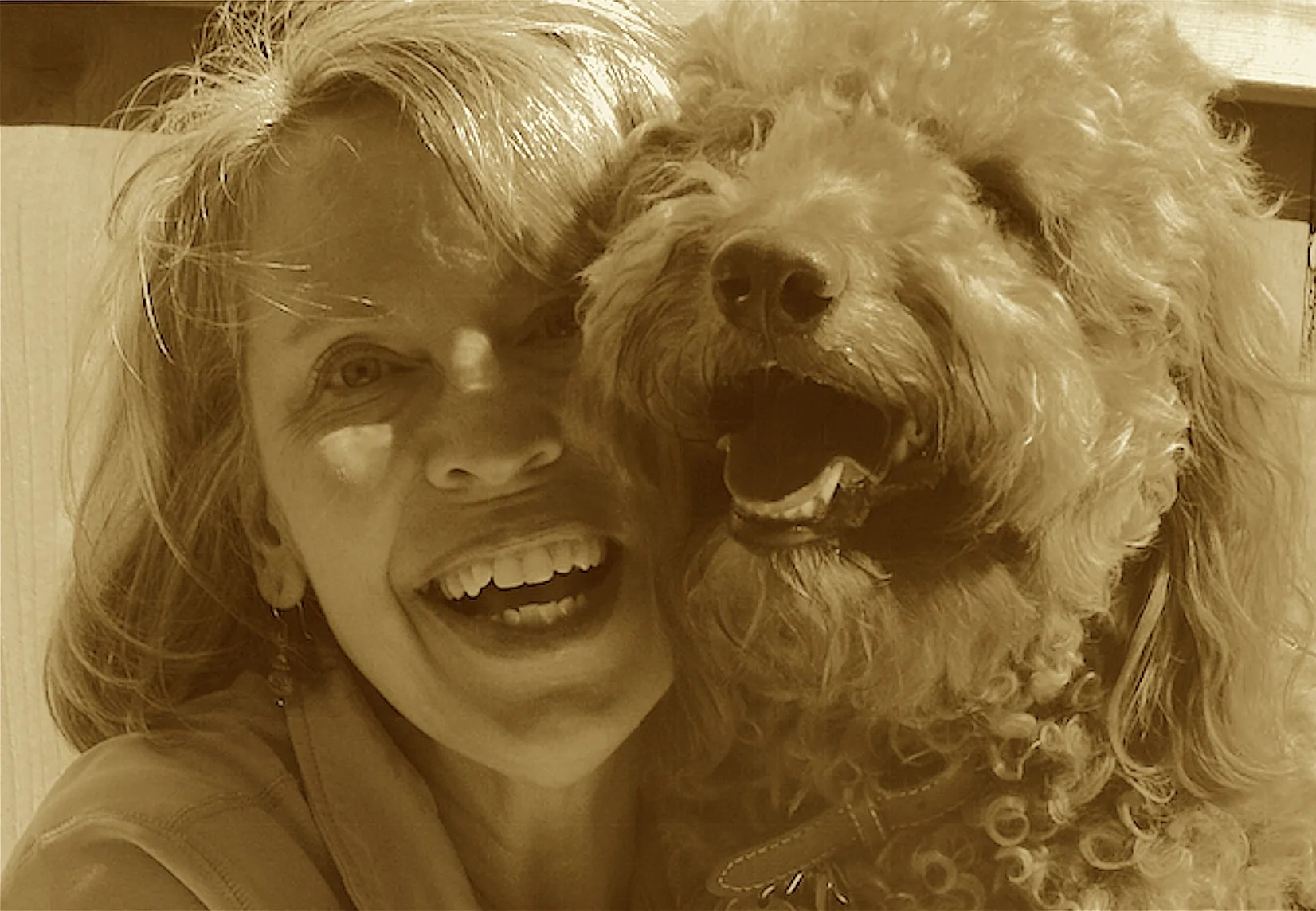 Goldendoodle dog and Goldendoodle mom smiling together. photo.