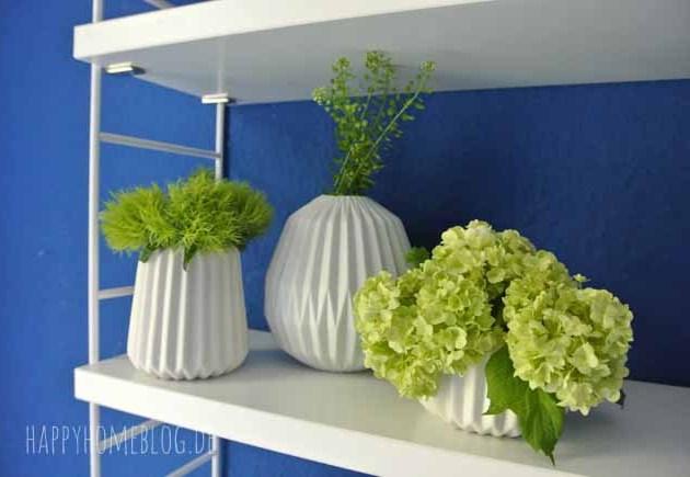 Grüne Blumen in weissen matten Porzellanvasen