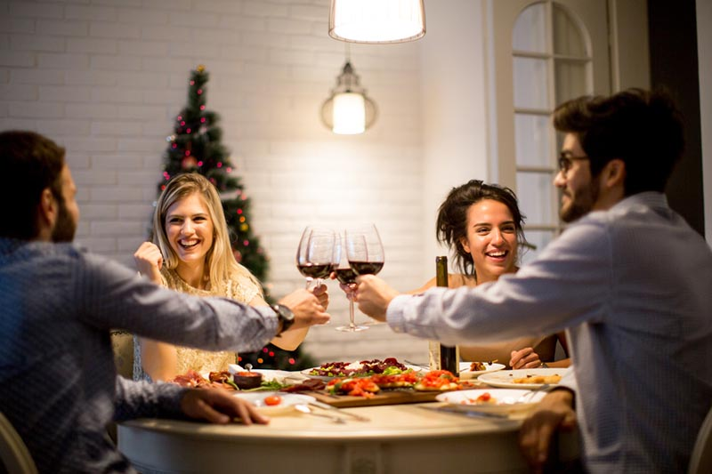 Group of young people celebrating New Year and drinking red wine