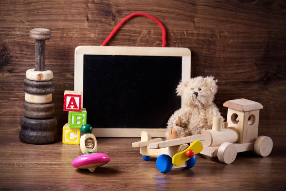 A collection of children's toys, including a wooden plane, a wooden train, a wooden top, wooden blocks, a wooden chalkboard, and a fluffy bear.