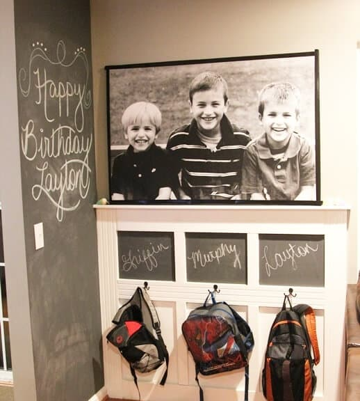 Family command center and chalkboard wall with hooks for book bags.